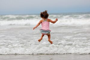 una bimba al mare salta felice, fare chiarezza dentro di sé è divertente