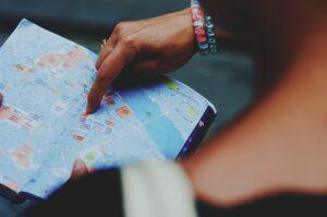 persona che indica un punto su una mappa - pianificare un viaggio senza contrattempi