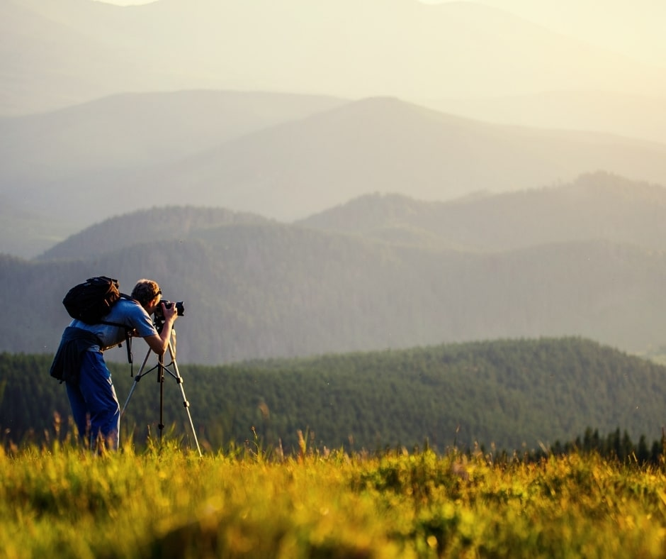 uomo che fotografa panorama montano-le vacanze disorganizzate fanno bene, meglio vivere l'avventura