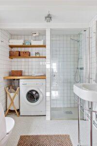 lavatrice a vista e mensole di fianco alla doccia