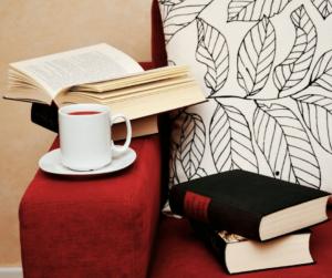 su un divano ci sono dei libri e un caffè
